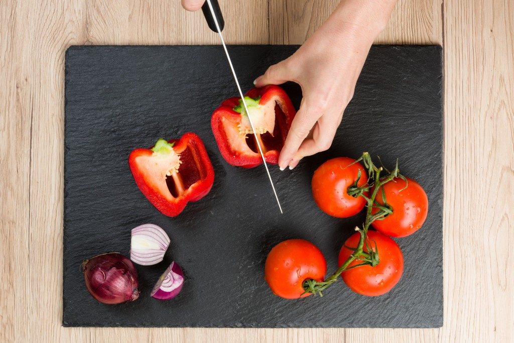 Top down view on cutting board with hands slicing vegetables