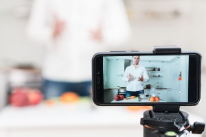 man recording a cooking show using a mobile phone